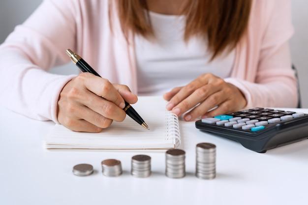 Sluit omhoog van aziatische vrouw die op notitieboekje met calculator en muntstukkenstapel op witte lijst schrijft