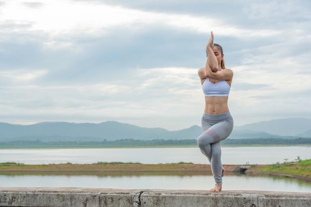 Sluit omhoog van aziatische vrouw die yoga doet stelt bij het strand.