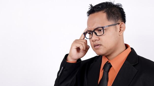 Sluit omhoog van aziatische zakenman die op witte achtergrond denken