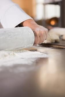 Sluit omhoog van bakker gebruikend een deegrol in de keuken van de bakkerij