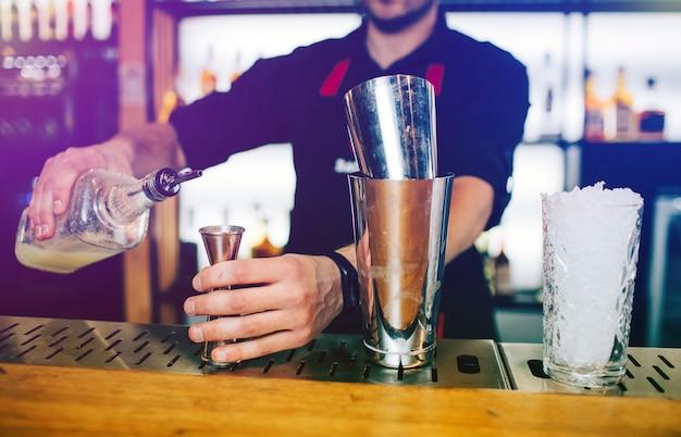 Sluit omhoog van barman die wat alcohol toevoegen aan de kleine kop en het houden. er staan twee bekers op de stand van de barman.