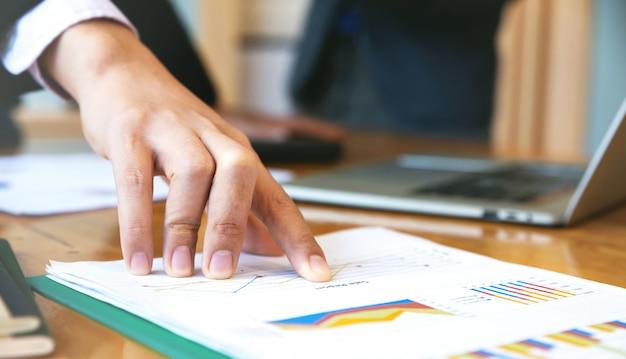 Sluit omhoog van bedrijfsmedewerkerhand richtend op bedrijfsdocument tijdens bespreking op vergadering. bedrijfsmensenbrainstorming bij bureau.
