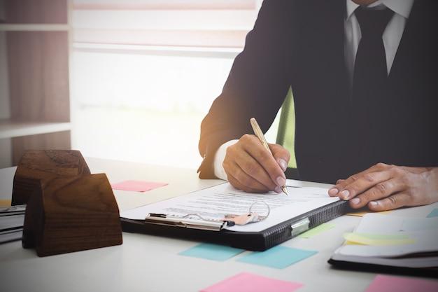 Sluit omhoog van bedrijfsmens die overeenkomst ondertekenen voor het kopen van huis. bank manager concept.