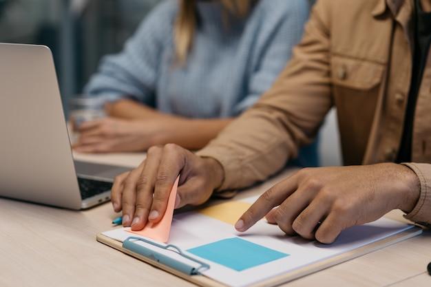 Sluit omhoog van bedrijfsmensenhanden houdend kleverige nota, werkend opstarten, plannend strategie, behendig gebruikend