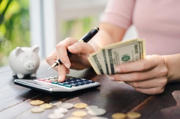 Sluit omhoog van bedrijfsvrouw met calculator tellend geld. geld besparen en financieel concept