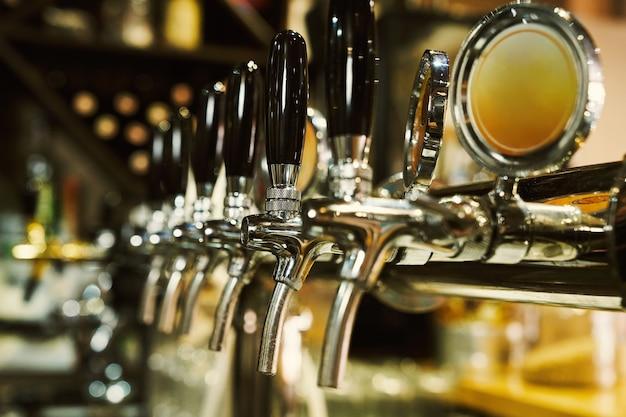 Sluit omhoog van biertap in rij. metalen uitrusting voor bar en minibrouwerij. concept van moderne apparatuur.