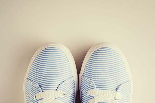 Sluit omhoog van blauwe gestreepte vrouwelijke tennisschoenen op een witte hoogste mening als achtergrond. plat leggen minimale achtergrond, getinte foto
