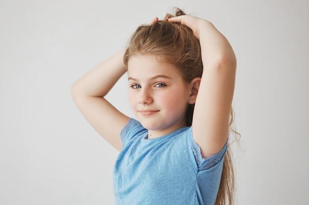 Sluit omhoog van blij blond klein meisje met blauwe ogen en rode wangen glimlachend, makend haar haar, klaar voor school