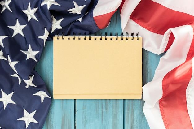 Sluit omhoog van blocnote op houten achtergrond, amerikaanse vlaggen van de vs.