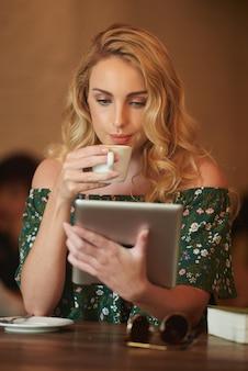 Sluit omhoog van blonde vrouw die het web op het digitale stootkussen doorbladert terwijl het drinken van koffie in een koffie