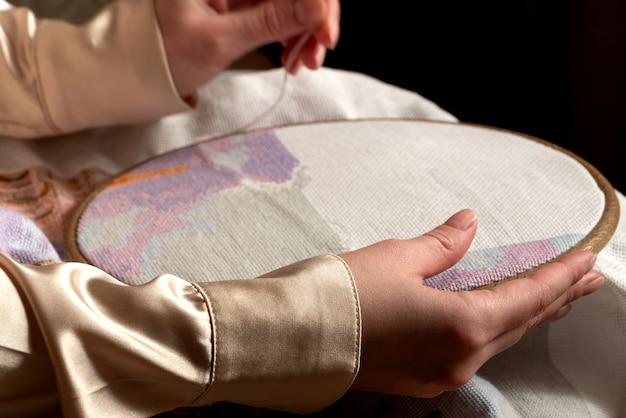 Sluit omhoog van borduurwerkkader in handen, vrouw die handwerk doet. kruissteken, hobby, doe-het-zelf