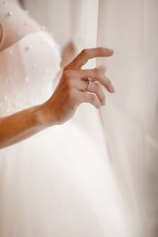 Sluit omhoog van bruid die voor de huwelijksdag voorbereidingen treft. luxe bruids jurk close-up.