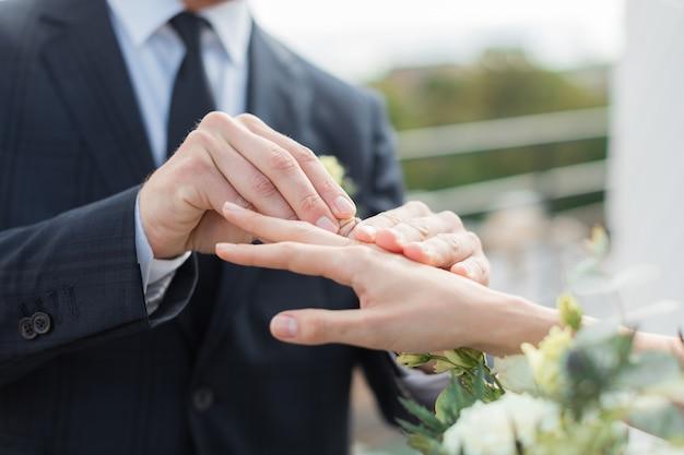 Sluit omhoog van bruidegom die gouden ring op de vinger van de bruid zetten