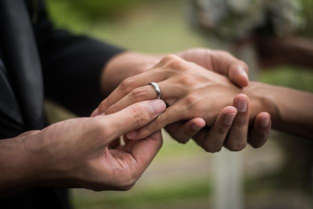 Sluit omhoog van bruidegom draagt de ringsbruid in huwelijksdag. liefde, gelukkig huwelijkconcept.