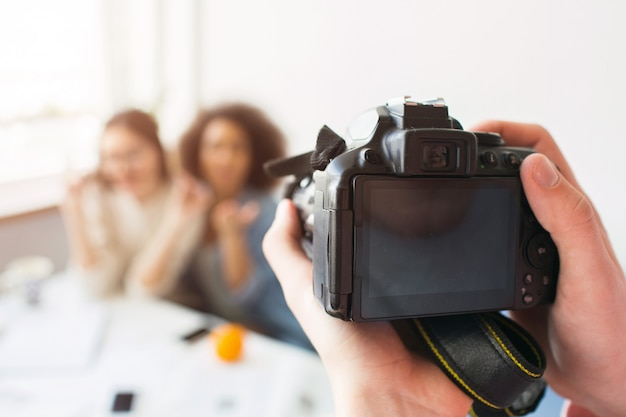 Sluit omhoog van camera die klaar is om een foto van twee mooie meisjes te nemen. iemands handen houden het vast.
