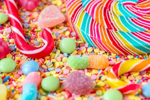 Sluit omhoog van candycane en lolly op een kleurrijke snoepjesachtergrond