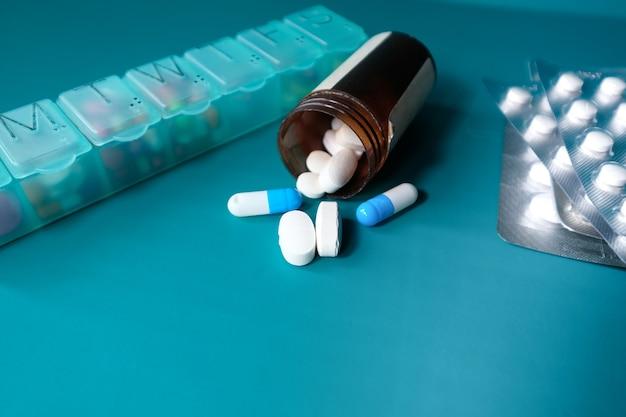 Sluit omhoog van capsule en pillen die op groene achtergrond morsen.