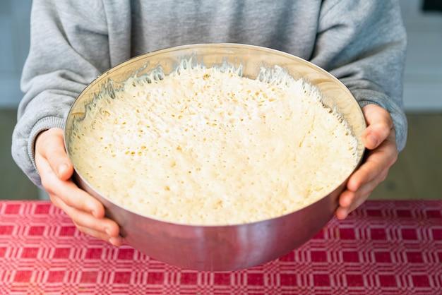 Sluit omhoog van chef-kok die deeg voorbereidt voor het koken van brood of pizza.
