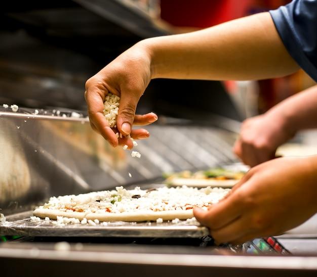 Sluit omhoog van chef-kok die kaas op pizzadeeg zet dat met tomatensaus wordt behandeld
