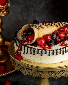 Sluit omhoog van chocolade druipende cake die met verpakte wafel met bessen wordt bedekt