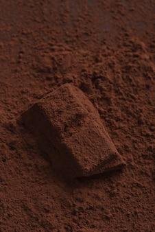 Sluit omhoog van chocoladesuikergoed dat met donker poeder wordt behandeld