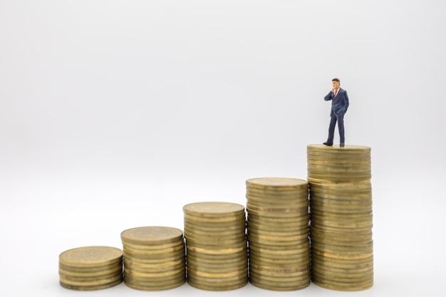 Sluit omhoog van cijfer die van zakenman het miniatuurmensen zich bovenop stapel gouden muntstukken op witte achtergrond bevinden.