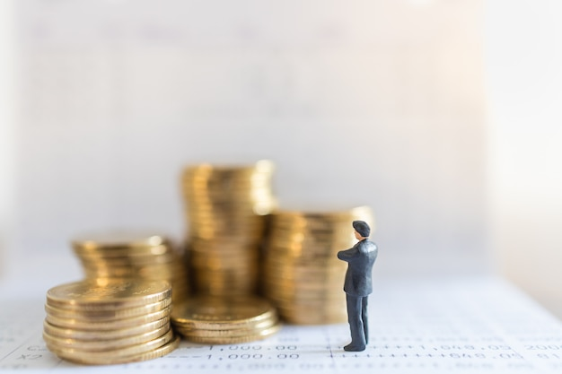 Sluit omhoog van cijfer van zakenman het miniatuurmensen status met stapel gouden muntstukken op bankbankboekje met exemplaar sapce.