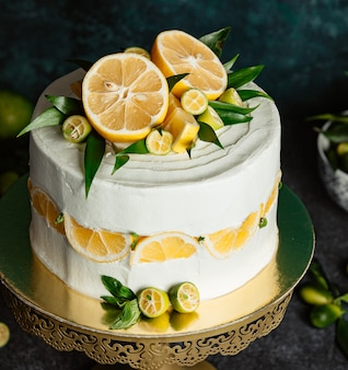 Sluit omhoog van citroencake die met citroen en kleine groene citroenen wordt bedekt