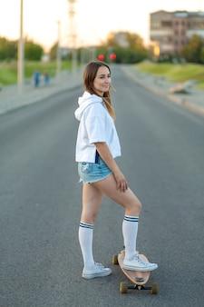 Sluit omhoog van damebeen in witte tennisschoenen die na extreme grappige rit rusten haar houten longboardskateboard. moderne stedelijke hipster meisje veel plezier. goede zonnige zomerdag om te skateboarden en plezier te hebben