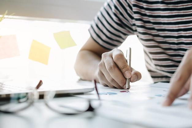 Sluit omhoog van de analysebedrijf van de de investeringsadviseur van de zakenman jaarlijks de balansverklaring van het financieel rapport het werken