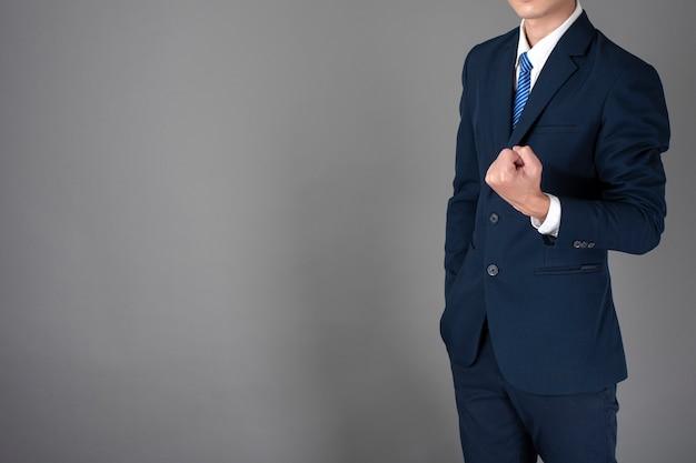 Sluit omhoog van de bedrijfsmens in blauw kostuum is succesvol op grijze achtergrond