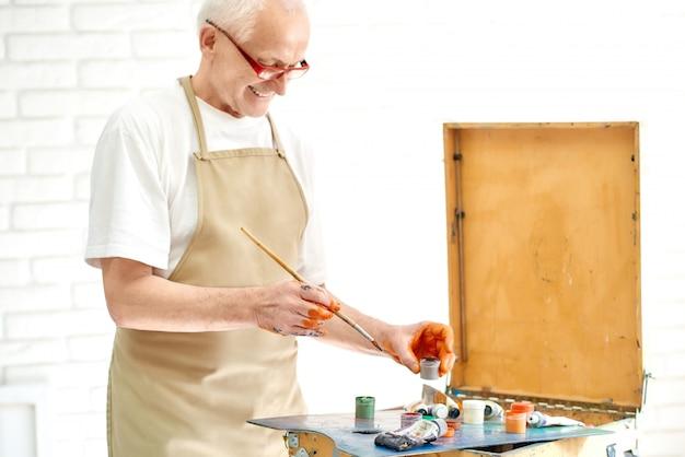 Sluit omhoog van de bejaarde knappe mens die verven kiezen die hij heeft nodig om het nieuwe schilderen in heldere studio te schilderen.