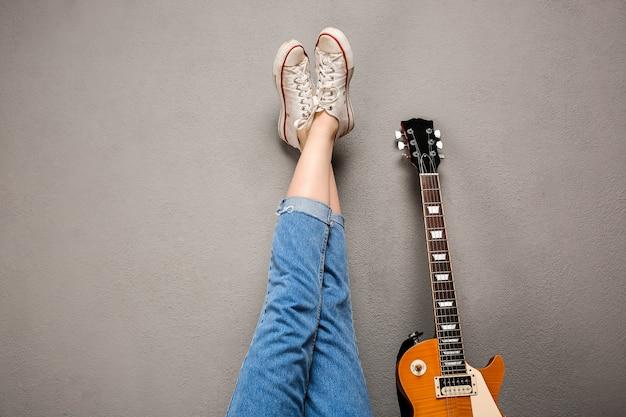 Sluit omhoog van de benen en de gitaar van het meisje over grijze achtergrond.