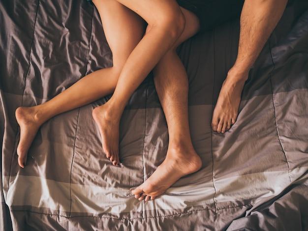 Sluit omhoog van de benen van een paar op het bed.