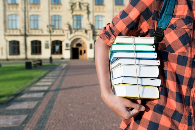 Sluit omhoog van de boeken van de tienerholding onder zijn wapen