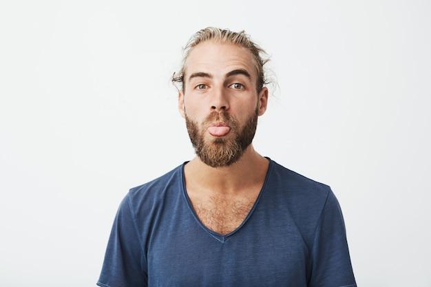 Sluit omhoog van de grappige knappe mens met goed kapsel en baard die in blauw t-shirt dwaas gezicht maken