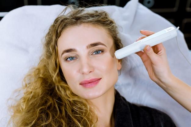 Sluit omhoog van de hand die van de artsenschoonheidsarts anti het verouderen procedure in cosmetologiebureau doen. tevreden jonge vrouw liggend op de bank, glimlachend en ontspannen