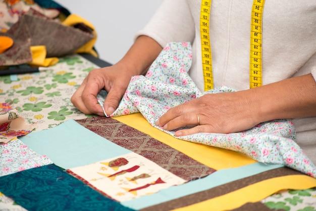 Sluit omhoog van de hand naaiend lapwerk van de vrouw