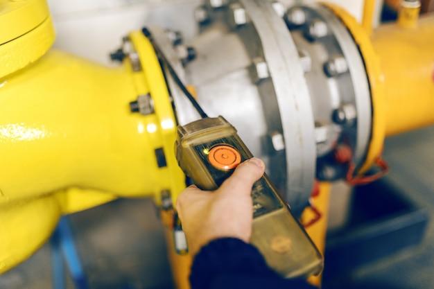Sluit omhoog van de hand van de arbeider het drukken knoop in verwarmingsinstallatie.