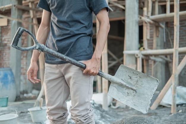 Sluit omhoog van de hand van een bouwer die een schop draagt naar een onvoltooid gebouw van een huis
