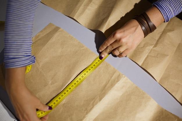 Sluit omhoog van de hand van een naaister met een centimeter