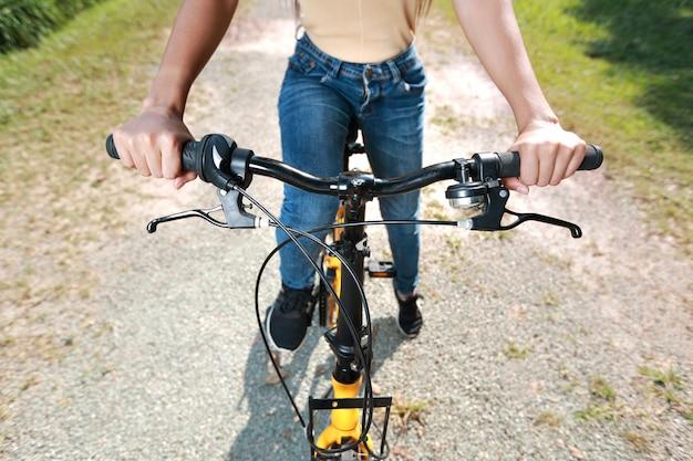 Sluit omhoog van de handen die van de hipstervrouw fiets berijden en pret onder aardstraat hebben