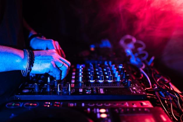 Sluit omhoog van de handen die van dj een muzieklijst in een nachtclub controleren.