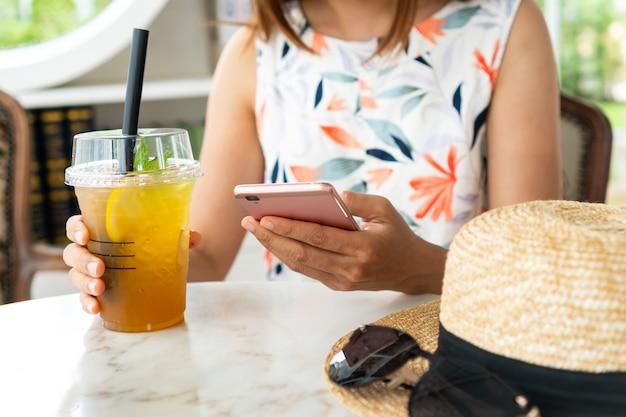 Sluit omhoog van de handen die van vrouwen dranken houden terwijl het gebruiken van mobiele telefoon in koffie.