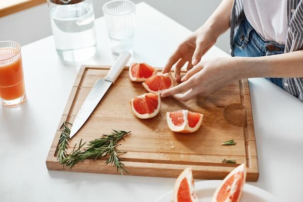 Sluit omhoog van de handen gesneden grapefruitmes en rozemarijn van het meisje op houten bureau. kopieer ruimte.