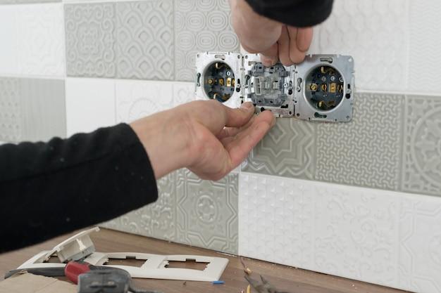 Sluit omhoog van de handen van de elektricien installeerend afzet op muur