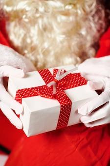 Sluit omhoog van de handen van de kerstman met giftdoos