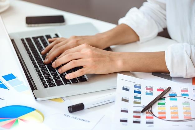 Sluit omhoog van de handen van de onderneemster typend op laptop bij werkplaats.
