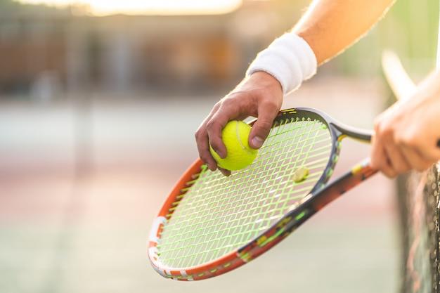 Sluit omhoog van de handen van de tennisspeler holding racket met bal.
