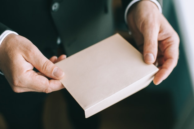 Sluit omhoog van de handen van de volwassen ernstige man met een witte envelop zonder inscripties.